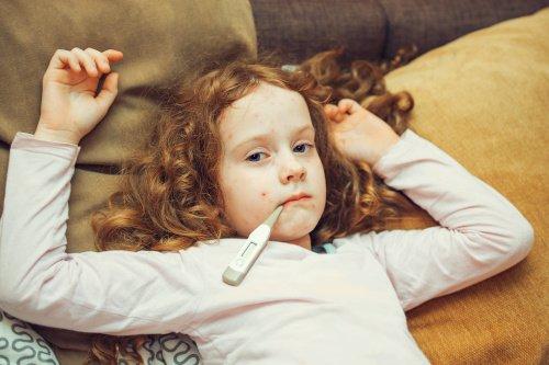 Mädchen mit Masern und Thermometer im Mund