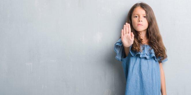 Maedchen signalisiert mit erhobener Hand und ernsten Gesicht Stop
