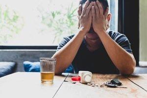 Mann stützt Gesicht in Hände, vor ihm Pillen und Alkohol