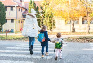 Mutter mit zwei Kindern auf dem Schulweg
