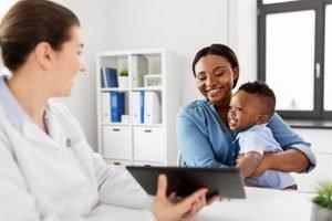 junge Mutter sitzt mit Kind bei einer Ärztin
