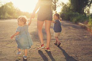 Mutter hat zwei kleine Kinder an der Hand