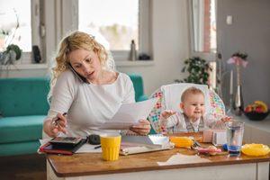 Mutter stellt Berechnungen an, Baby im Hochstuhl daneben