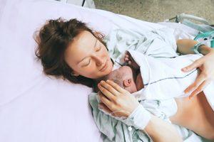 Mutter haelt Neugeborenes direkt nach der Geburt