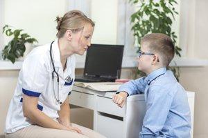 Physiotherapeutin erklärt kindlichem Patienten den Ablauf der Behandlung
