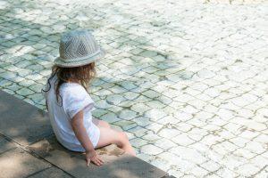 Ein Kind sitzt im Schatten.