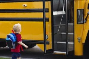 kleiner Junge geht auf Schulbus zu