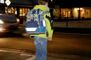 Kind mit reflektierenden Stellen am Ranzen im Dunkeln