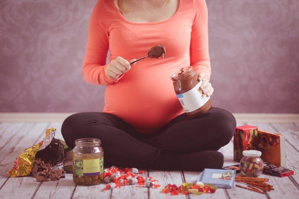 Schwangere Frau isst Süßigkeiten