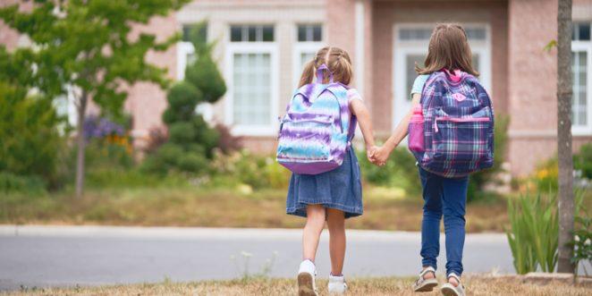 zwei Mädchen Hand in Hand auf dem Schulweg