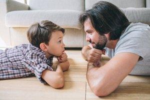 Sohn und Vater liegen auf dem Boden udn schauen sich an