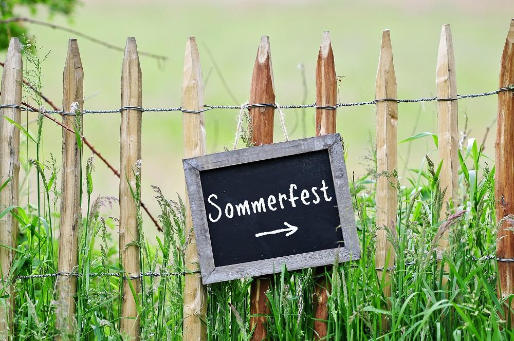 Schild Sommerfest im Kindergarten an Holzzaun
