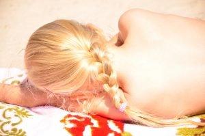 Ein Kind schläft am Strand in der Sonne.