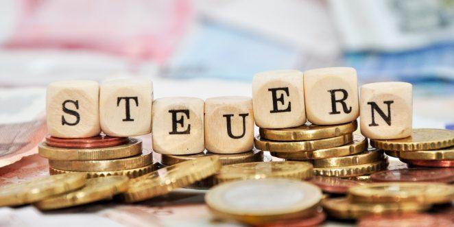 Kleingeld auf dem Holzklötze das Wort Steuern bilden
