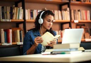 junge Frau sitzt in Bibliothek vor Laptop