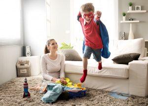 Kind springt im Superhelden-Outfit von der Couch