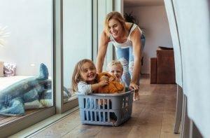 Mutter schiebt Kinder im Wäschekorb