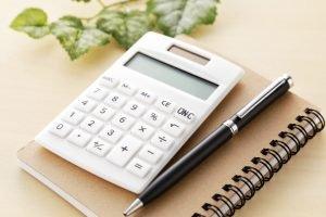 Taschenrechner liegt neben Kugelschreiber auf braunem Notizbuch. Im Hintergrund eine Pflanze