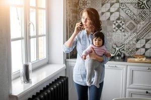 Mutter telefoniert mit Baby im Arm