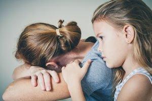 kleines Mädchen umarmt Mutter, die mit abgewandtem Gesicht weint