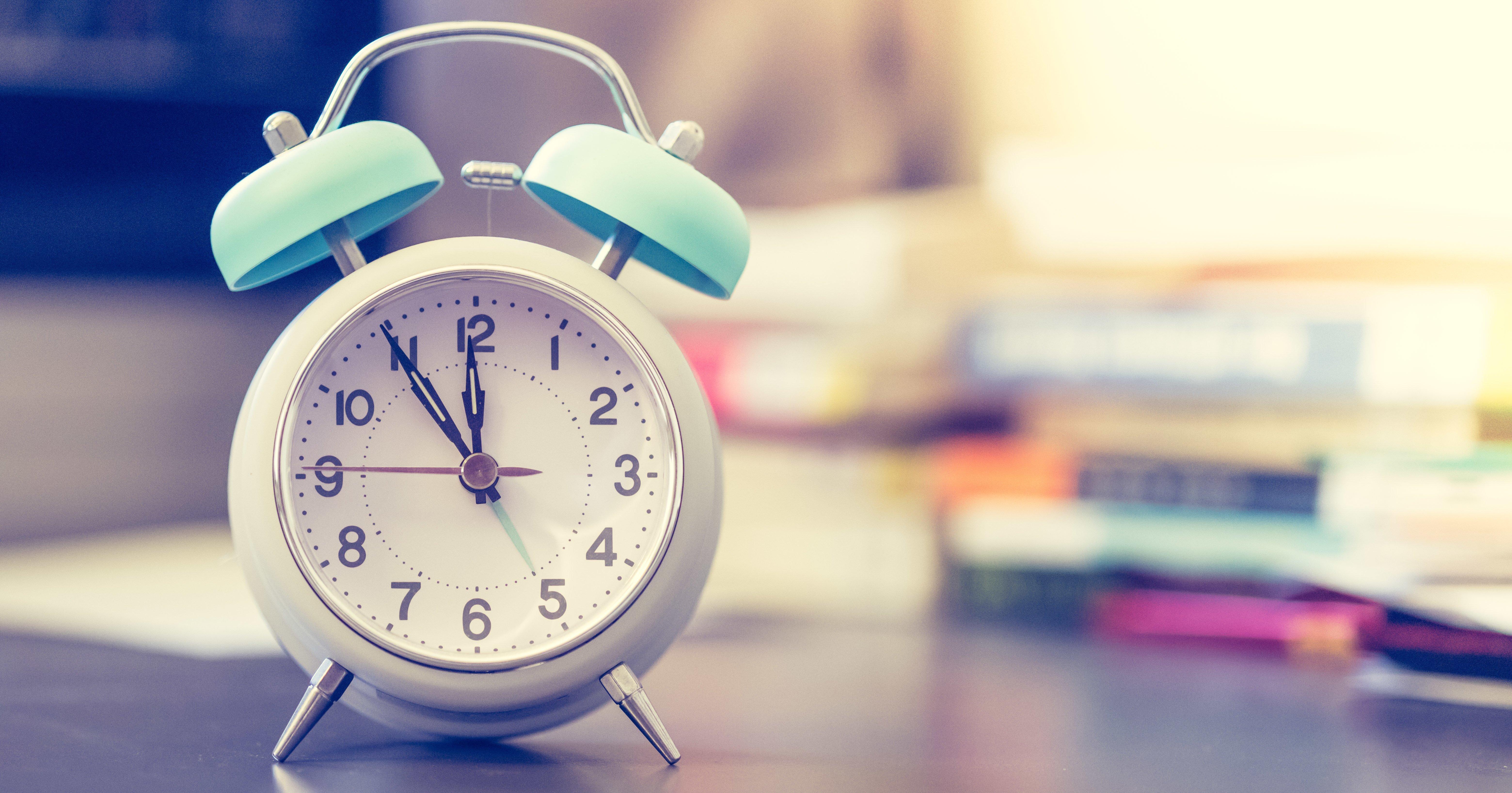Wecker auf Schreibtisch, Bücher im Hintergrund, Breitbild