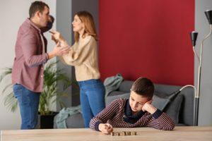 streitendes Paar, davor Junge mit Münzen