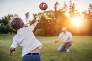 Junge und Vater spielen Ball