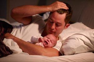 Vater mit weinendem Baby im Bett