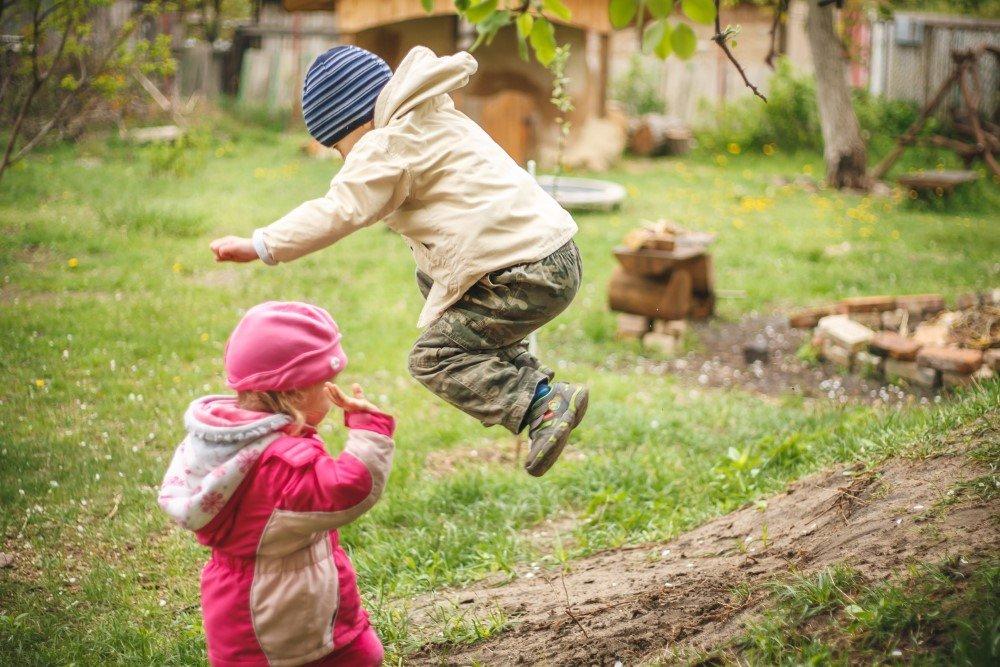 Kinder springen in Natur herum