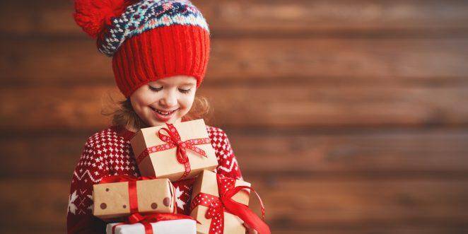 Kind mit Weihnachtsgeschenken im Arm