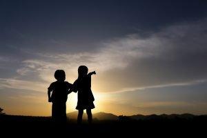 Kinder stehen im Abendlicht