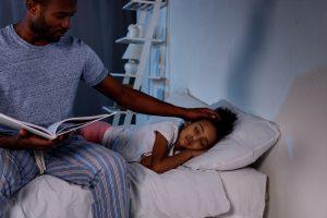 Vater mit seinem kleinen Mädchen in einem abgedunkelten Raum