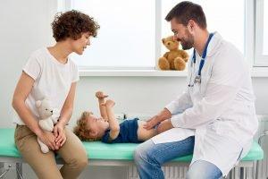 Kinderarzt tastet den Bauch eines Jungen in einer Untersuchung ab