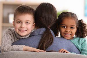 Mutter hält 2 Kinder im Arm, die unterschiedliche Hautfarben haben