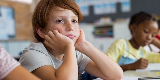 kind schaut verträumt im Unterricht