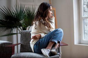 Frau sitzt traurig und zusammengekauert auf einem Stuhl
