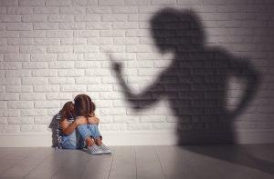 ängstliches Kind sitzt vor einer Wand, Mutter als bedrohlicher Schatten