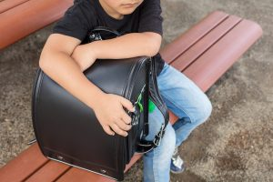 ein aengstliches kind sitzt mit dem schulranzen auf einer bank