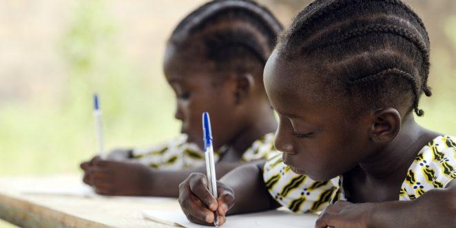 zwei afrikanische Kinder lernen an einem holztisch