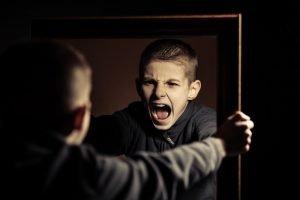 aggressives Kind schreit sein Spiegelbild an