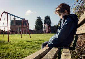 Kind sitzt allein auf einer Bank neben dem Spielplatz