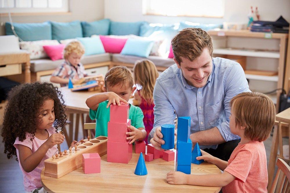 Erzieher spielt mit Kindern an einem Tisch