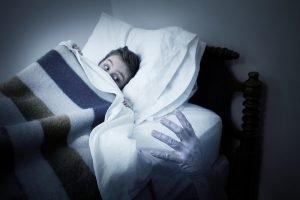 Hand kommt unter dem Bett eines Kindes hervor