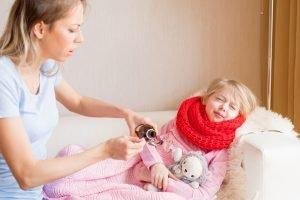 mutter gibt ihrem kranken kind antibiotika-saft