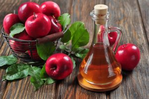 Äpfel und Apfelessig auf einem Tisch