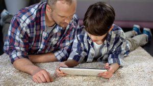 Vater übt zusammen mit seinem Sohn am Tablet