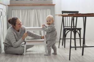 Mutter unterstützt Baby beim Aufstehen lernen