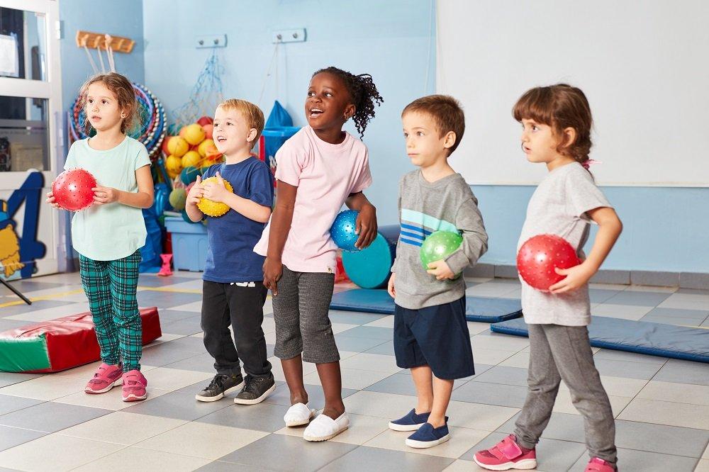 Kinder stehen mit Bällen in einer Reihe