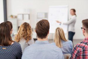Frau hält einen Vortrag am Flipchart vor einer Gruppe