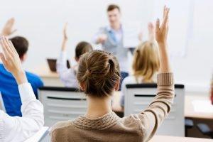 Frau meldet sich im Unterricht